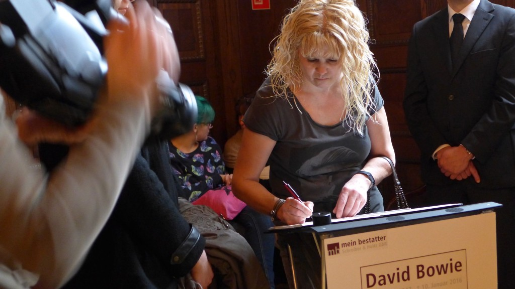 A fan signs the Condolence Book. Photo: Megan Spencer (c) 2016
